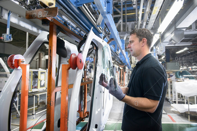 Car worker wearing protective gloves fitting sheet of glass into vehicle door on production line in car factory