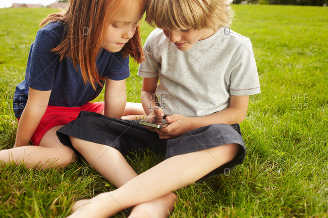 Children using cell phone in grass