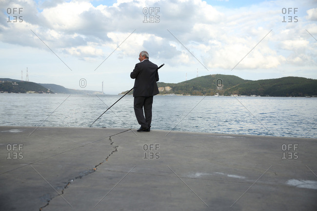 Istanbul, Turkey - October 25, 2014: Man in suit fishing off the shores of Istanbul