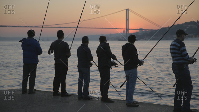 Istanbul, Turkey - November 4, 2014: Group of young men fishing off the shores of Istanbul