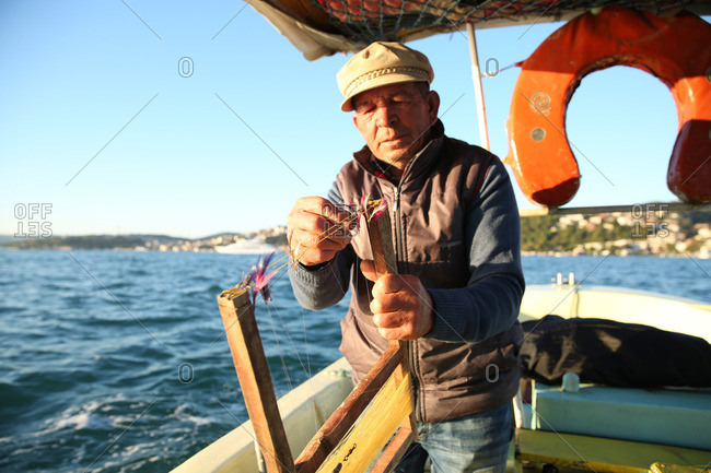 Istanbul, Turkey - September 30, 2014: Fisherman preparing feather lures and hooks on a boat off of the coast of Turkey