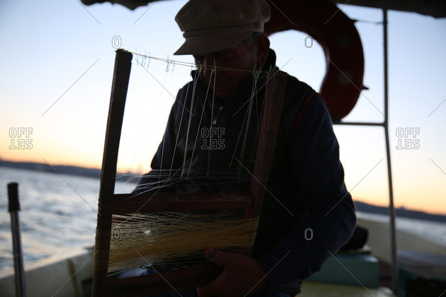 Istanbul, Turkey - September 30, 2014: Fisherman preparing hooks and fishing line on a boat off of the coast of Turkey