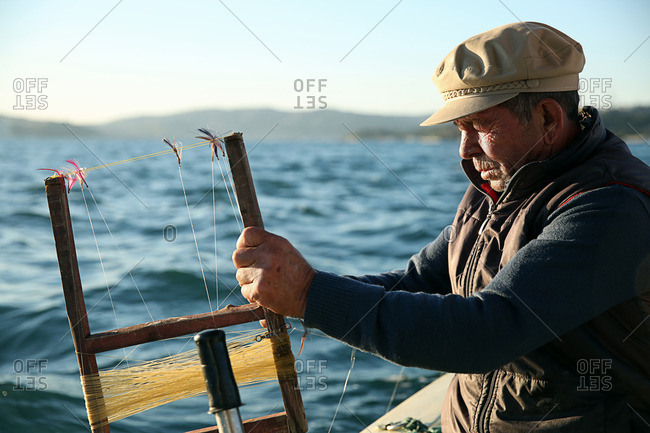 Istanbul, Turkey - September 30, 2014: Fisherman preparing his lures and hooks on a boat off of the coast of Turkey