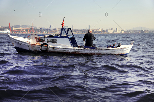Istanbul, Turkey - November 6, 2014: Fisherman fishing on his boat off the shores of Turkey