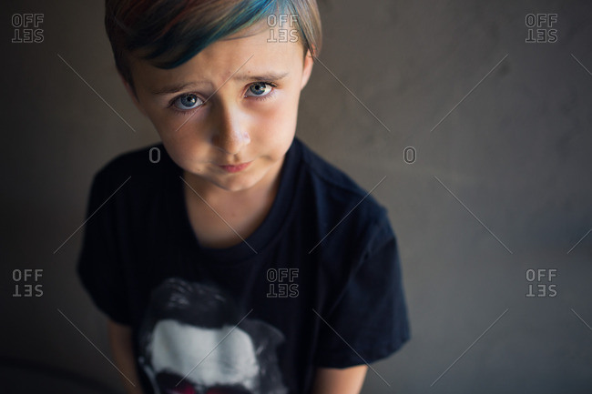 Portrait of a boy with dyed hair and a graphic t-shirt