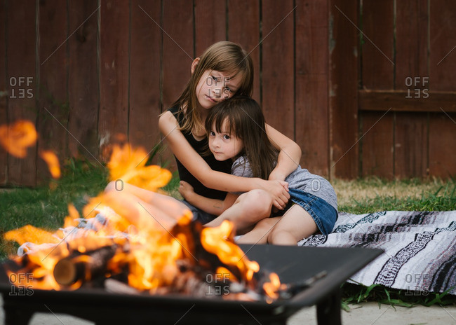 Sisters cuddling by a bonfire