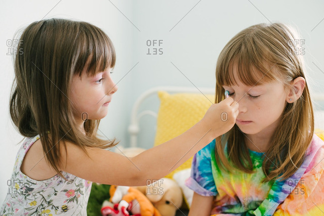 Little girls putting makeup on each other