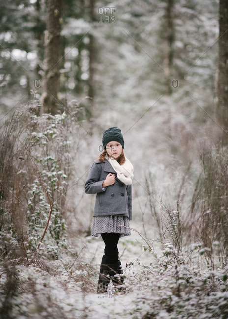 Girl standing in snow forest