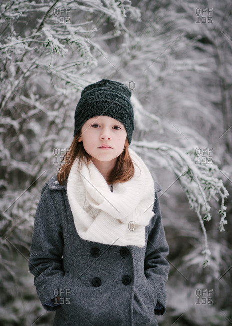 Portrait of a girl standing in snow forest