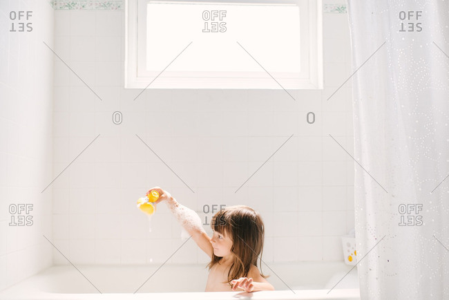 Little girl playing in bathtub with a rubber ducky