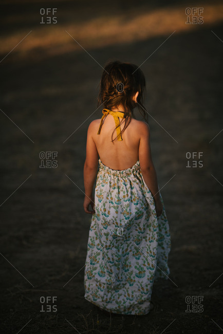 Little girl standing in sunset light wearing summer dress