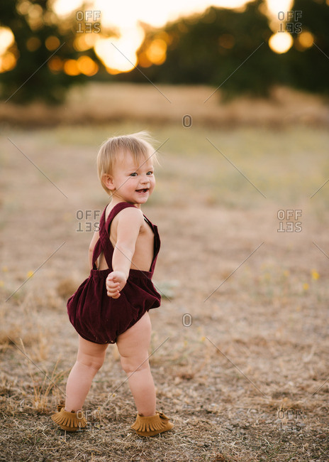 Happy baby girl wearing maroon jumper