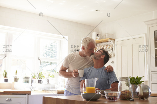 Middle aged gay male couple kissing in their kitchen