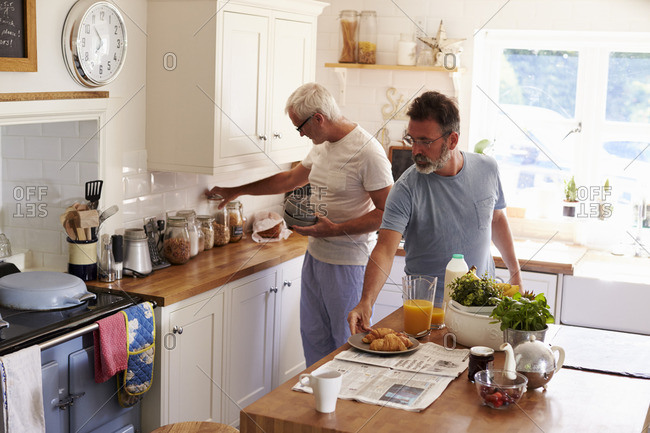 Male gay couple preparing breakfast in their kitchen