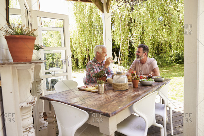 Gay male couple sitting down for lunch on their patio