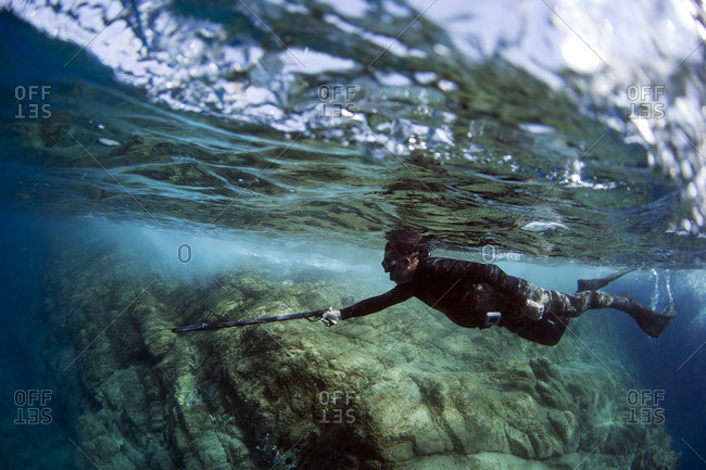 Underwater view of a diver spearfishing at coral reef