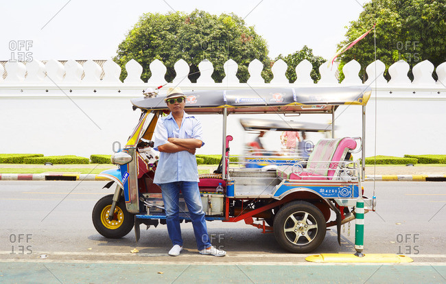 Bangkok, Thailand - March 31, 2016: Local tuk-tuk driver in front of the Grand Palace