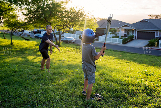 Man pitches baseball to son at dusk