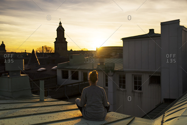 Woman on roof looking at sunset