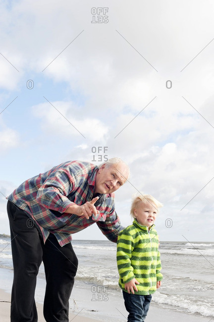 Grandfather with grandson standing on beach