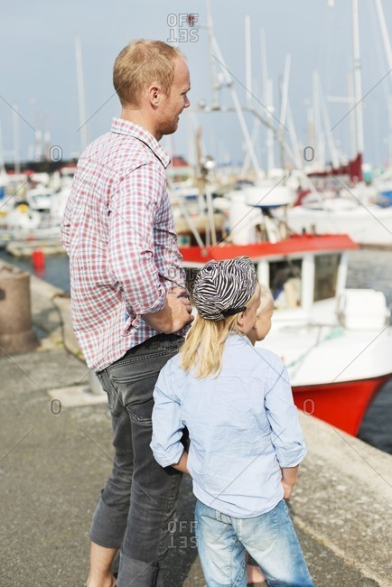Father with kids standing in marina and looking at tourboats
