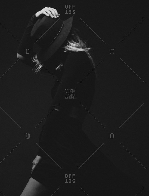 Model covering face with hat