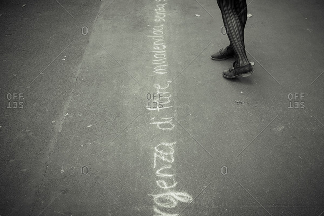 Woman by writing on ground, Italy