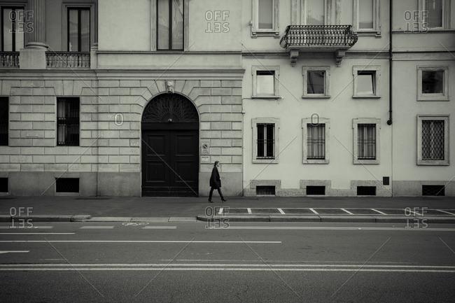 October 7, 2011: Woman walking on sidewalk, Italy