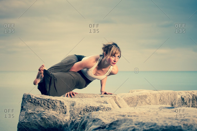 October 31, 2012: Woman doing yoga on boulder