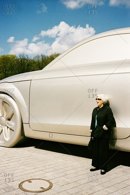 September 22, 2006: Middle-aged woman posing in front of big ideas sculpture of an oversized giant silver car
