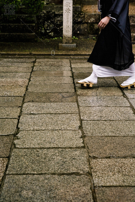 Monk in traditional robes and wooden Geta sandals walking on a stone pathway