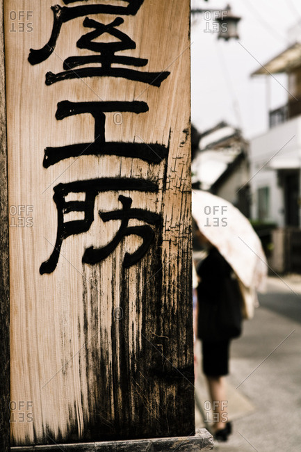 Woman holding umbrella behind wooden sign in Naramachi, Japan