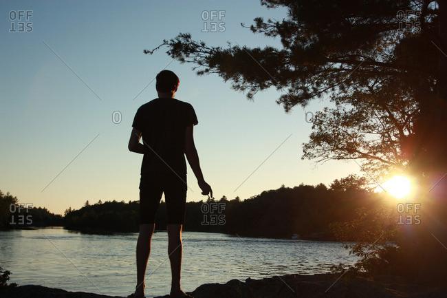 Man standing along a lake at sunset