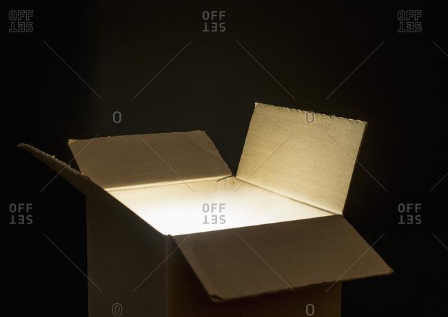 Open cardboard box with glowing light inside