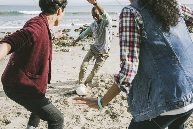 Group of friends kicking ball on a beach