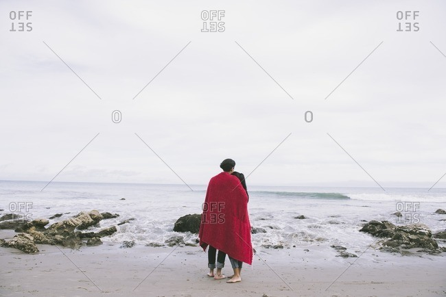 Young couple snuggling under blanket by the ocean