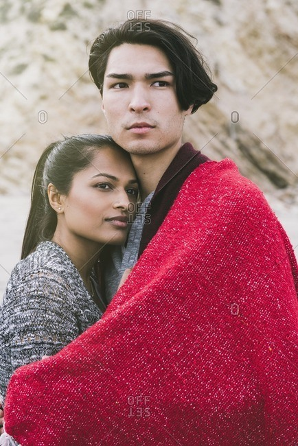 Young couple cuddling under a red blanket outdoors