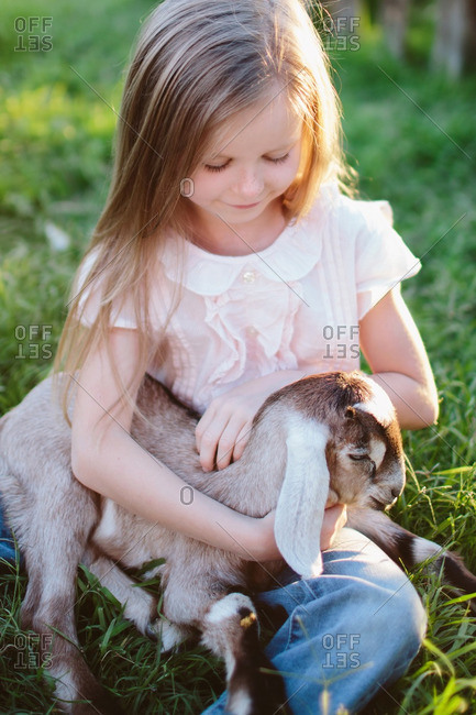 Little girl petting a baby goat