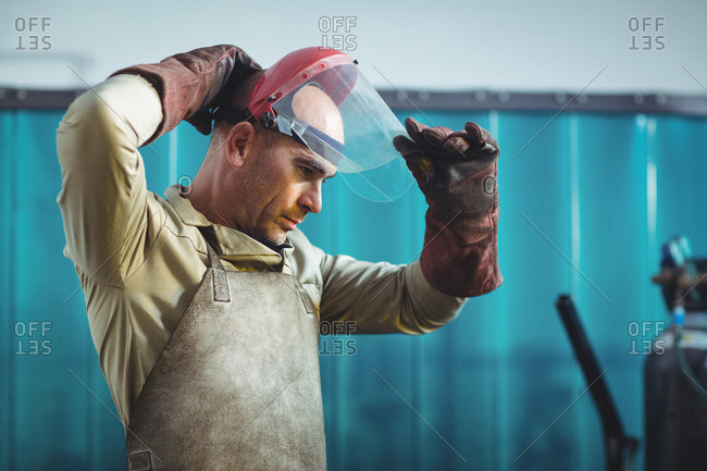 Male welder wearing protective helmet in workshop