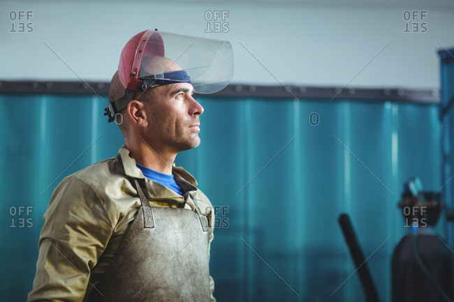 Male welder standing and looking away in workshop