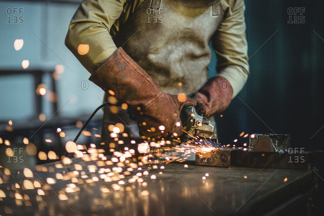 Mid-section of male welder working on a piece of metal in workshop