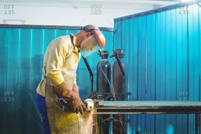 Male welder working on a piece of metal in workshop
