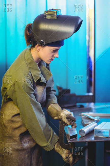 Female welder using clamp tool in workshop