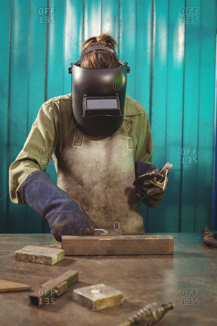 Female welder holding welding arch in workshop