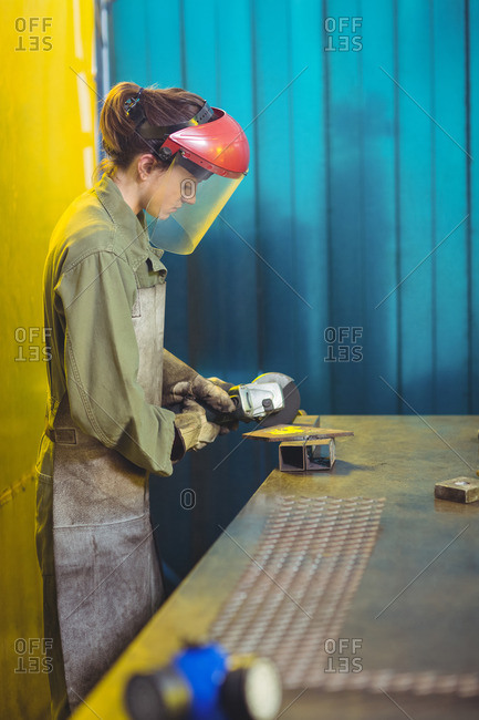 Female welder using circular saw in workshop