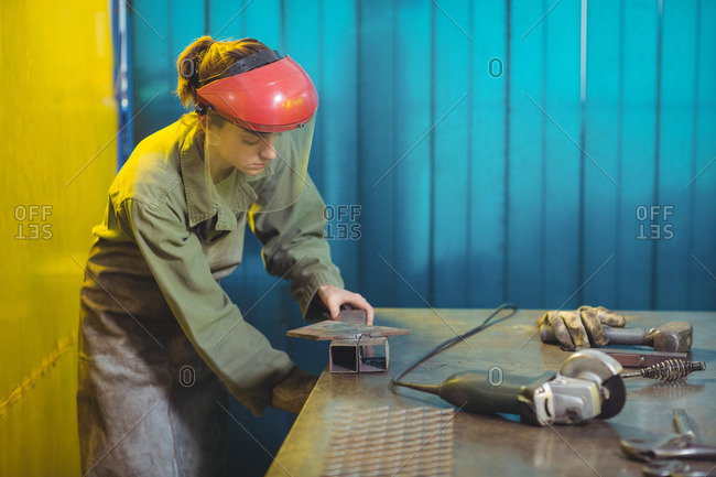 Female welder using a tool in workshop