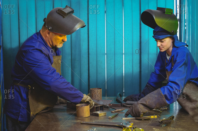 Male and female welders working together in workshop