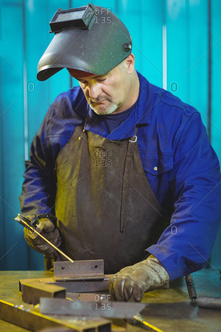 Male welder working on a piece of metal in workshop