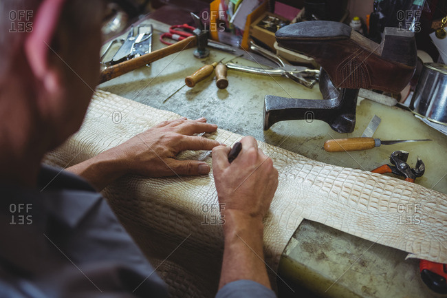 Shoemaker cutting a piece of material in workshop
