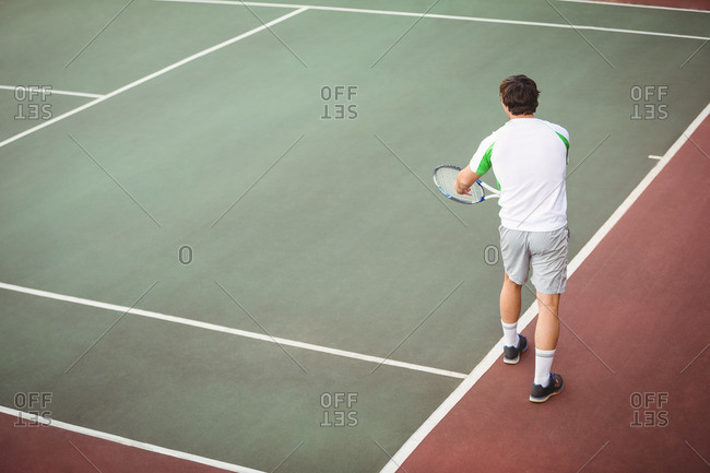Man with tennis racket ready to serve in the court
